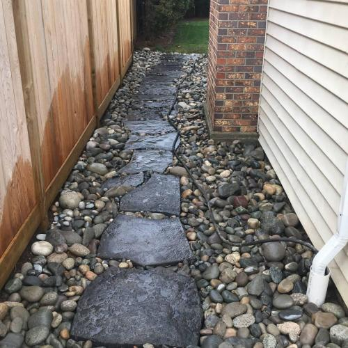 A stepping stone and river rock landscape finish after a drainage repair job.